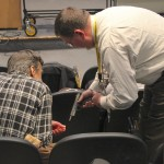 Firearms Expert Gene Clayton helping a participant in the audience learn about gun safety.